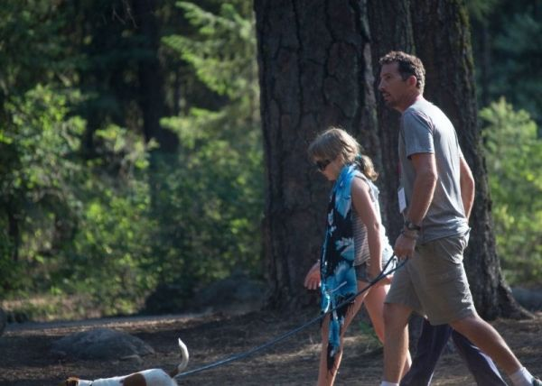 """Walking in the woods with Dad"" A candid photo of a father and daughter enjoying a walk in the woods with their dog."