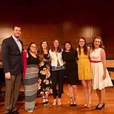 This is my with my voice teacher and fellow classmates at Rollins College. I am the one wearing the black dress with flowers.