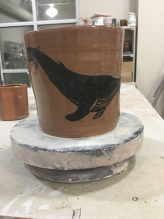 Hand painting whale on terra-cotta vessel