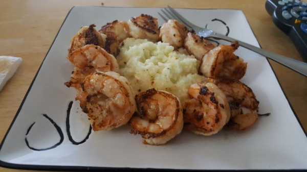 Garlic Shrimp served with sharp cheddar cheese grits with butter sauce.