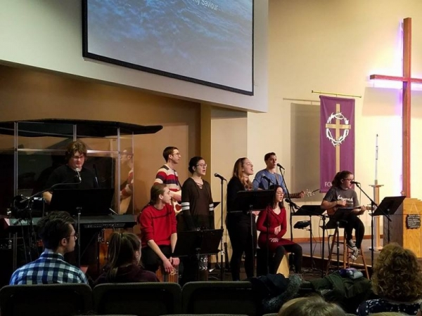 In this photo I am singing, wearing a black shirt. I am leading worship at my church.