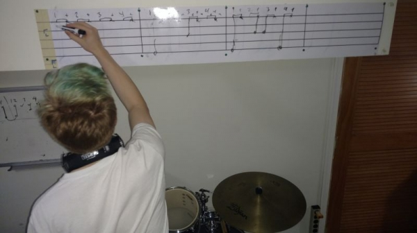 "Drum student ""M"" works out a a transcription of the beat to a song he's learning on the dry-erase sheet music above the Student Kit."