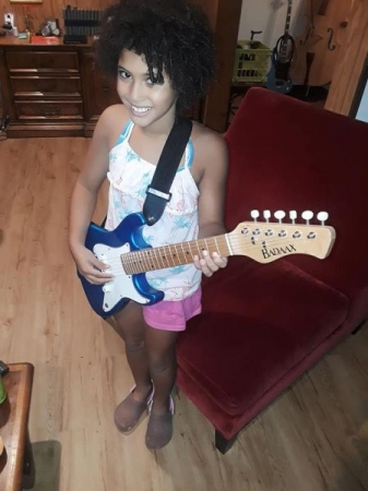 Samira, my violin and piano student, trying out a mini guitar