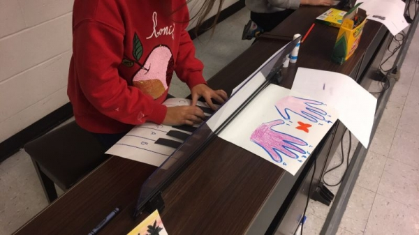 Students at the NJCU Community Music School creating paper pianos!