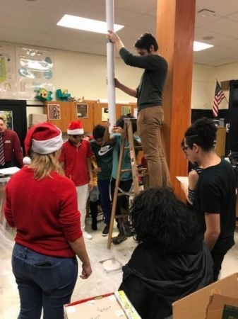 "Students participating in an ""ornament drop"", giving them hands-on experience with momentum and inertia in physics"