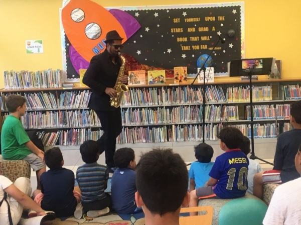 Damian J performing for summer camp students from the 1st grade at Shenandoah Miami's Public Library
