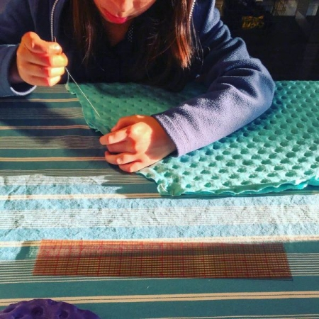 Hand sewing lesson- This student has chosen to continue with hand sewing for several months. Here she is sewing a mermaid tail blanket.