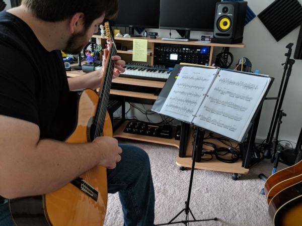 "Working on a solo guitar transcription of Debussy's ""Clair de Lune"" in my studio."