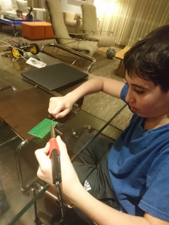 11 years old student soldering a DIY synthesizer circuit.