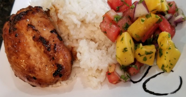 Grilled chicken thighs with jasmine rice and fresh mango salsa.