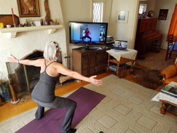 A student practicing virtual yoga safely from home with one of our yoga teachers.