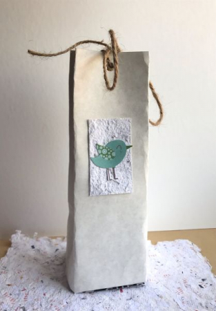 A handcrafted paper bag made with recycled cardstock, reclaimed material, and homemade paper!