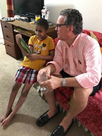 """Teaching Make-A-Wish kid Mohammed an interactive trick after performing his """"Wish Celebration party"""" in his family's apt."""