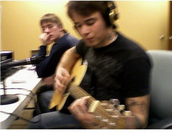 Using pro tools recording a song while friend looks on.