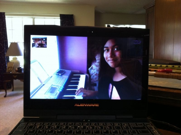 Student Mariya is reading the music on her iPad, playing the duet part on her mother's phone, and using a computer for her Skype lesson.