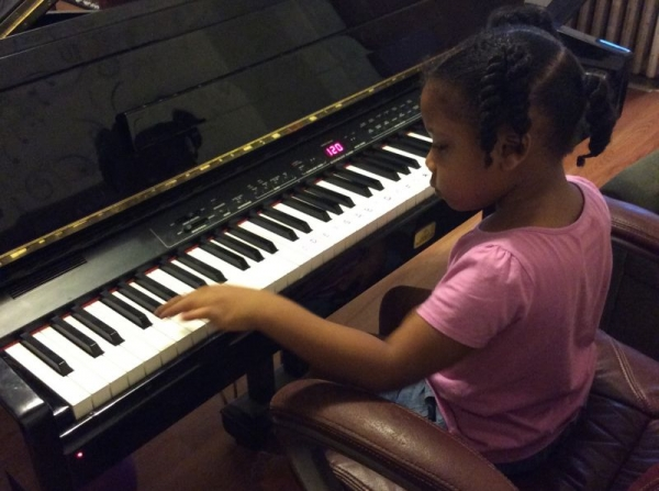 5 year old music student loves learn to play the piano