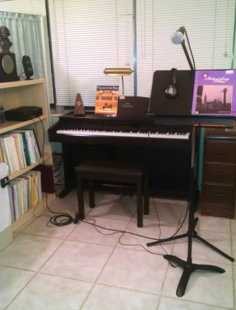 This is my studio. It has a Super Scope CD recorder, speakers, Yamaha keyboard,microphone, headphones, music stand, music books.