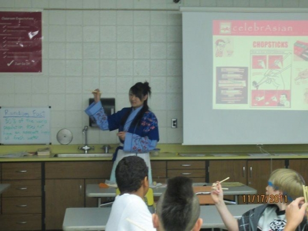 In the classroom, teaching 7th grade students how to use chopsticks.