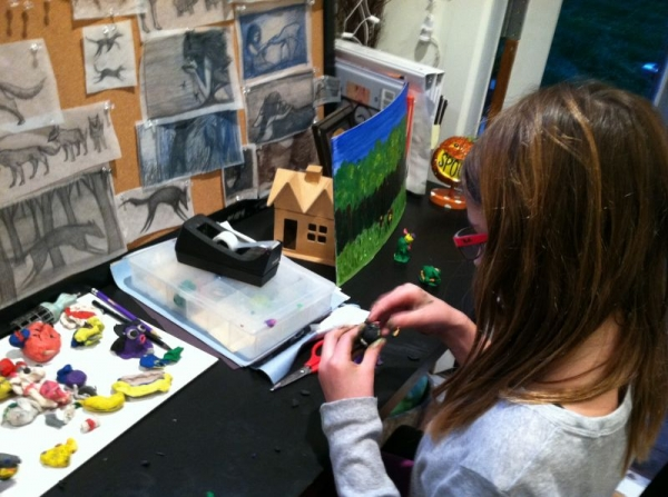 6th Grader working on a painting and clay project.