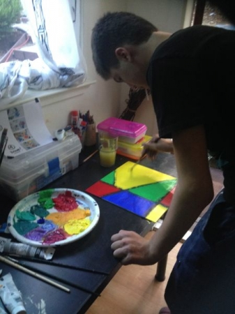9th Grader painting in acrylics a geometric abstract piece .