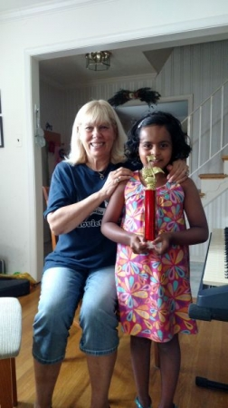 A student who received a trophy for her performance on the piano