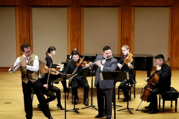 On stage in a chamber orchestra, accompanying a performance of Bach's Concerto for Two Violins, arranged for two flutes.